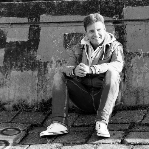 DJ Steve sitzt in Hamburg vor einer Wand