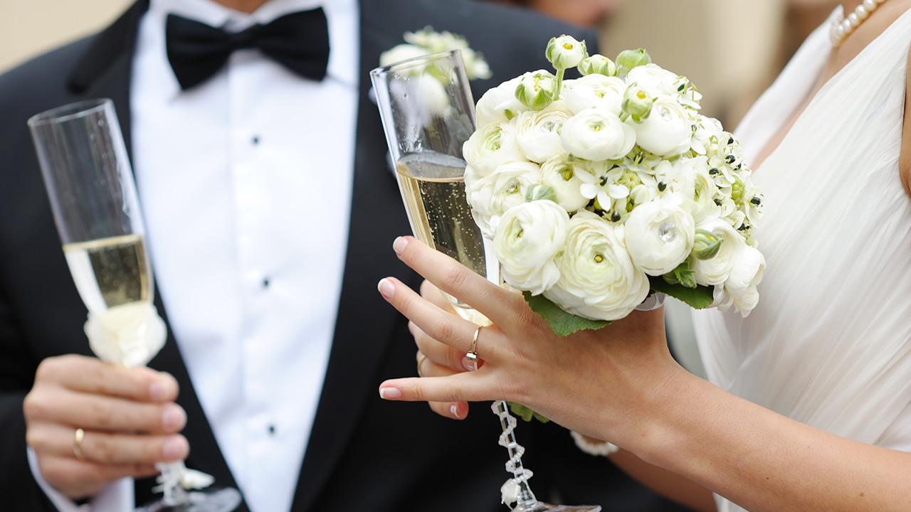 Hochzeitspaar mit Blumen und Sektgläsern Hochzeits DJ